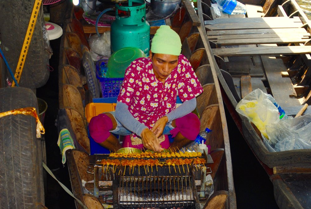 Chicken satay being sold from a boat in the floating market