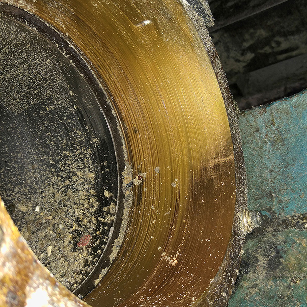 Worn brass sleeve in extruder hopper casting