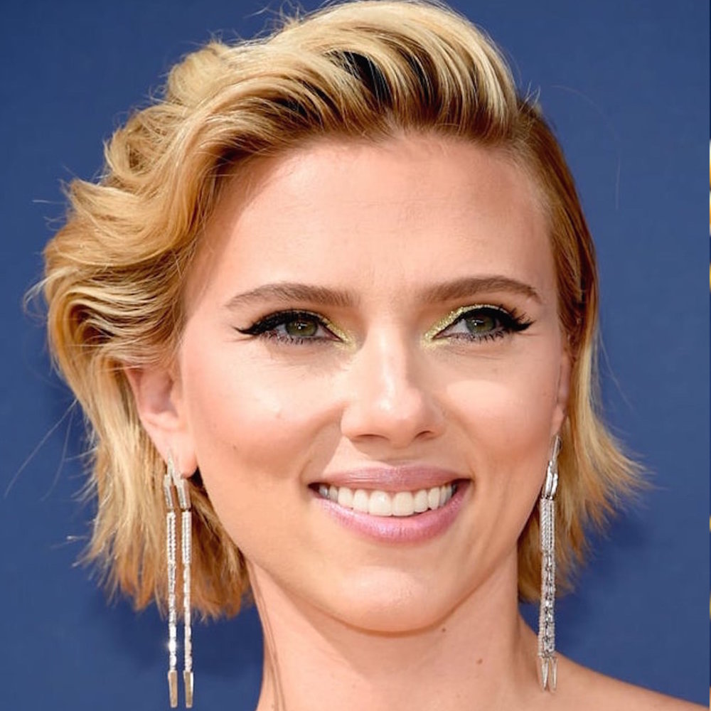 Another lady in white—actress Scarlett Johansson on the arm of her boyfriend, Emmy's co-host Colin Joust—caught our attention in dramatic Nikos Koulis shoulder-dusting, geometric Universe Line earrings in white diamonds and gold. The pointy shapes and inverted V's completed the deep neckline of her sequined Balmain gown. -
