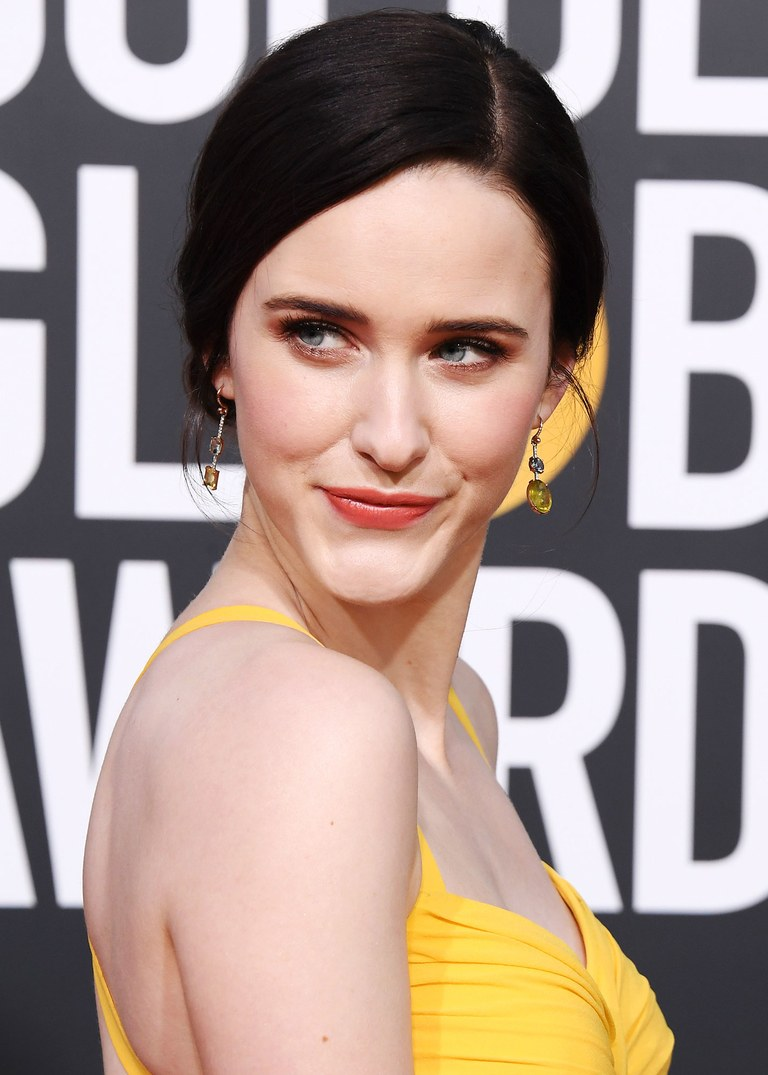 """""""Mrs. Maisel"""" (aka Rachel Brosnahan)accepted her award for her role in the Amazon Prime series wearing a custom Prada gown, highlighting its marigold hue with Irene Neuwirth one-of-a kind single earrings: Each dangler featured combinations of green and yellow tourmalines and pavé diamonds. She completed her look with a rainbow moonstone and sapphire bracelet, and rings made with moonstones, pink tourmalines and sapphires. -"""