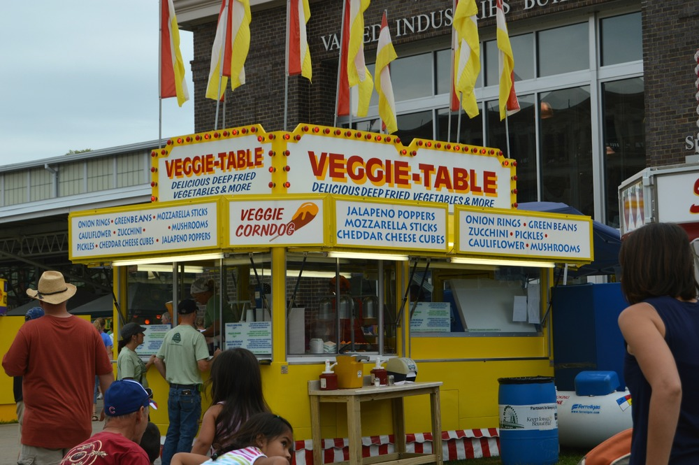 The Veggie Table at the Iowa State Fair. Three generations of the McCoy family proudly serving the famous veggie corn dog since 1982.