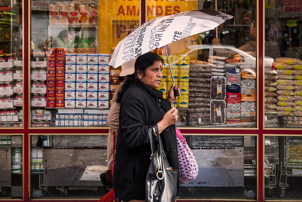Indian woman walks by shops on Rue Marx Dormoy.