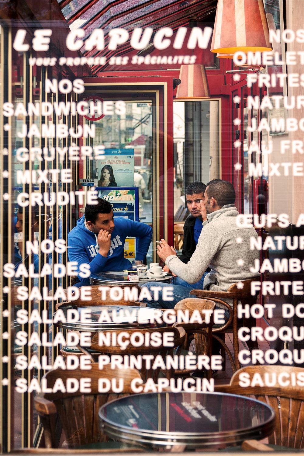 Men discussing at a classical parisian cafe on Place de La Chapelle.