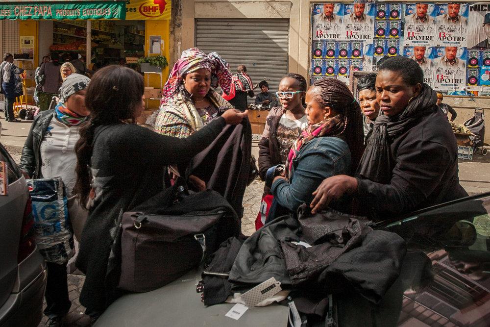 Women negotiate apparel goods in Rue des Poissonnieres.