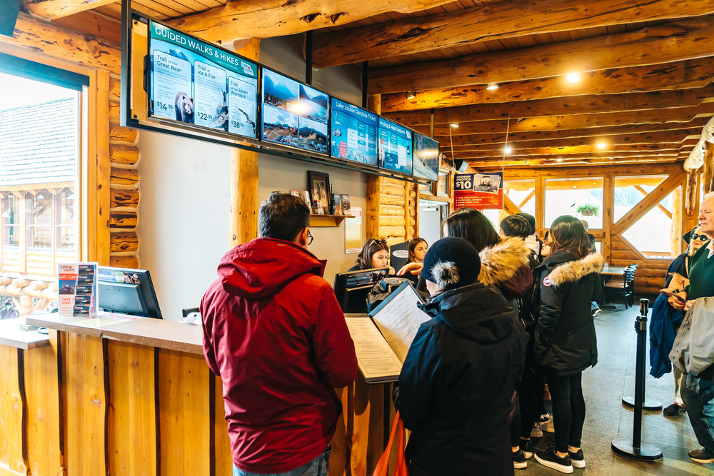 Purchasing tickets for the Lake Louise Summer Gondola & looking at the menus