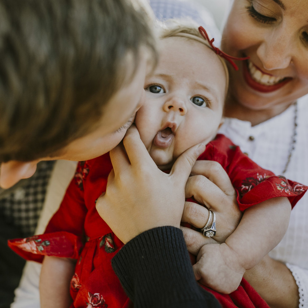 baby girl being held by mom and squished kissed by big brother funny family photo.jpg