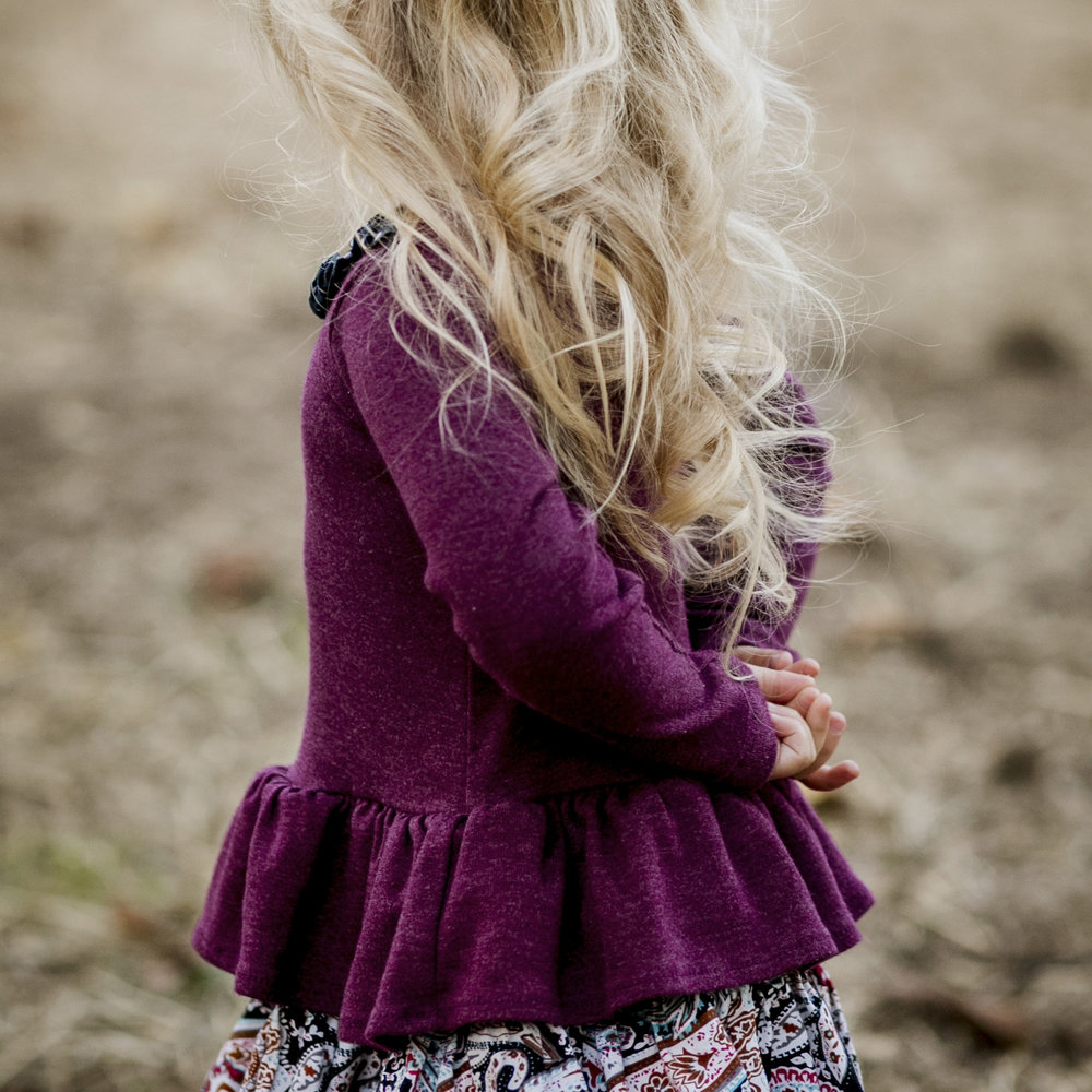 detail of little blonde girl with hands behind her back.jpg