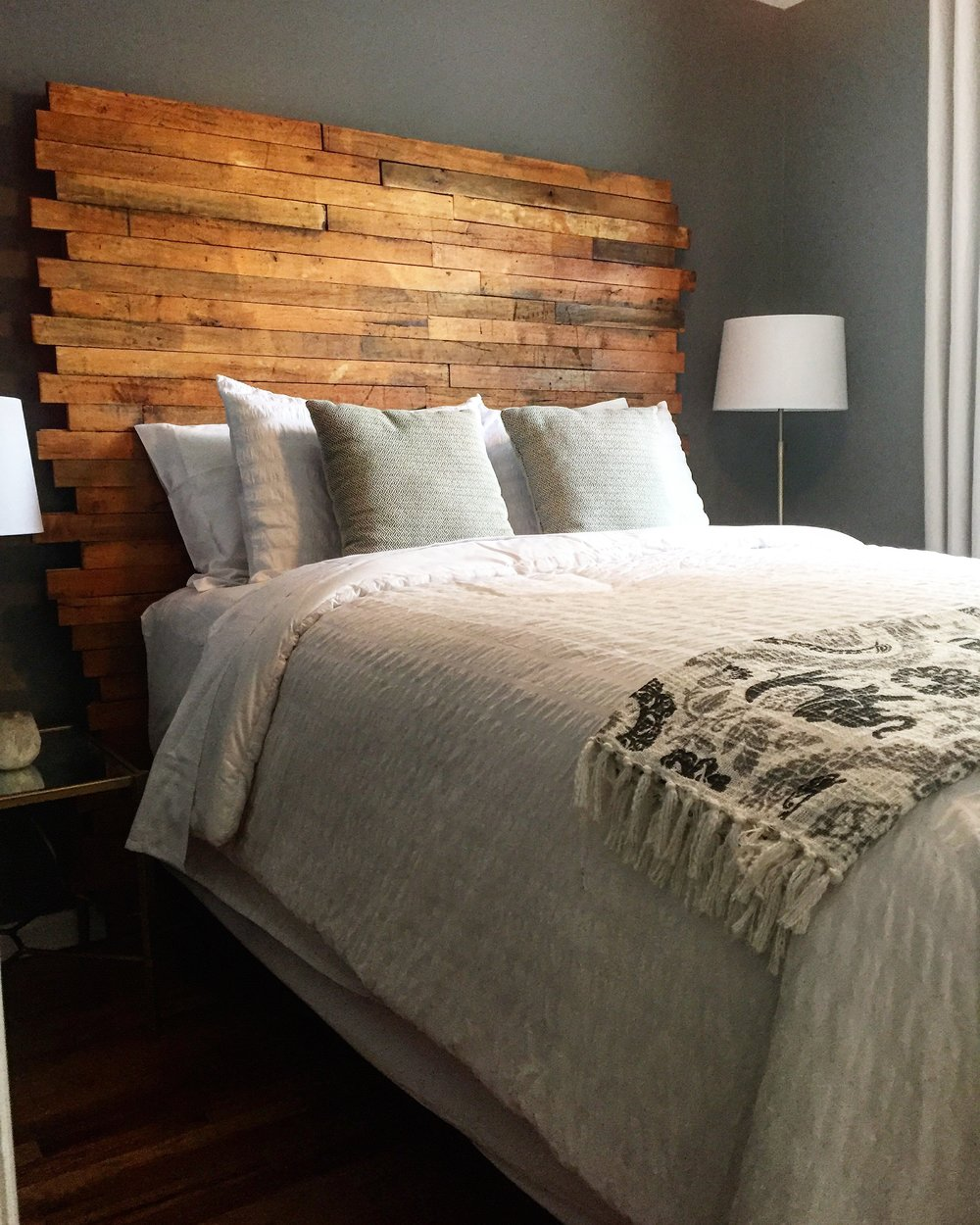 Custom headboard created for the guest bedroom. Made from old gym floor boards found in a building set for demolition in a small town in Nebraska.