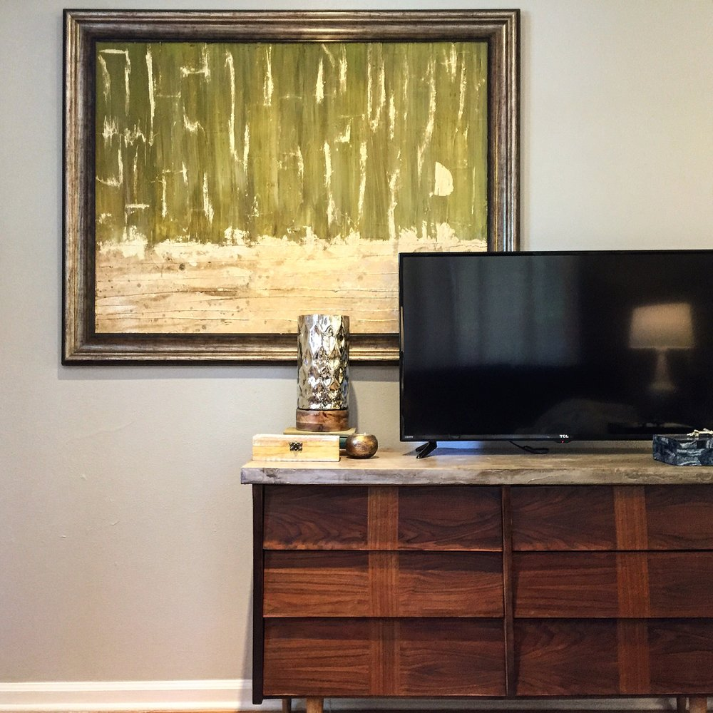 Custom artwork in the living room paired with this amazing Mid Century Modern dresser Cody found and refurbished. We then poured a new top out of cement to give a modern and durable twist to this classic item.