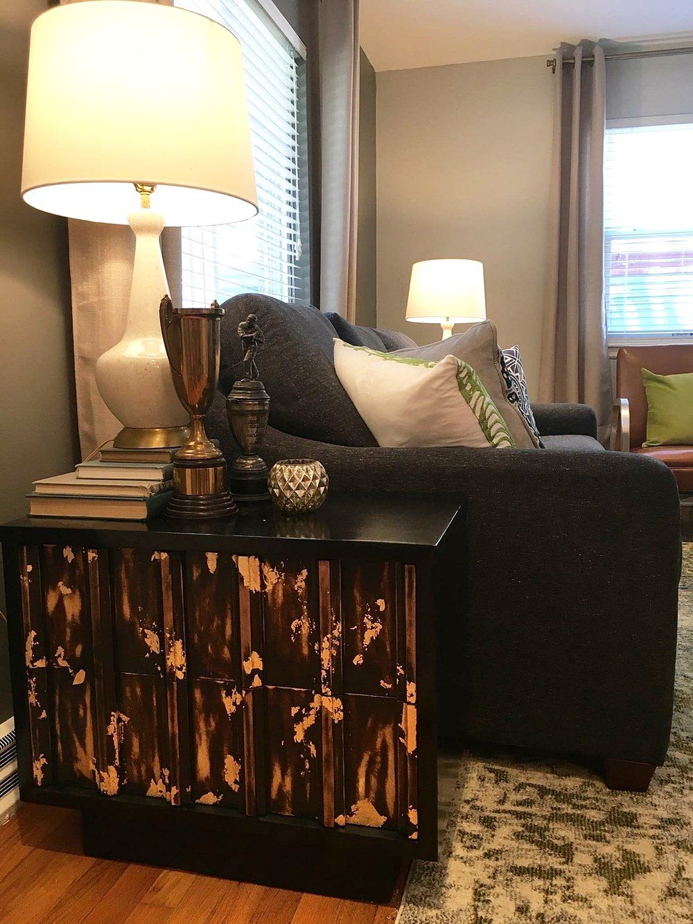 Custom made paint and stain side table with gold leaf accent. Paired with Mid Century Modern lamps, vintage books and antique trophies for a eclectic vibe.
