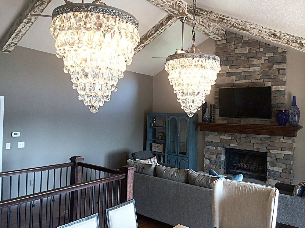 These custom raindrop crystal chandelier contrast beautifully against the new rustic modern floor to ceiling fireplace.