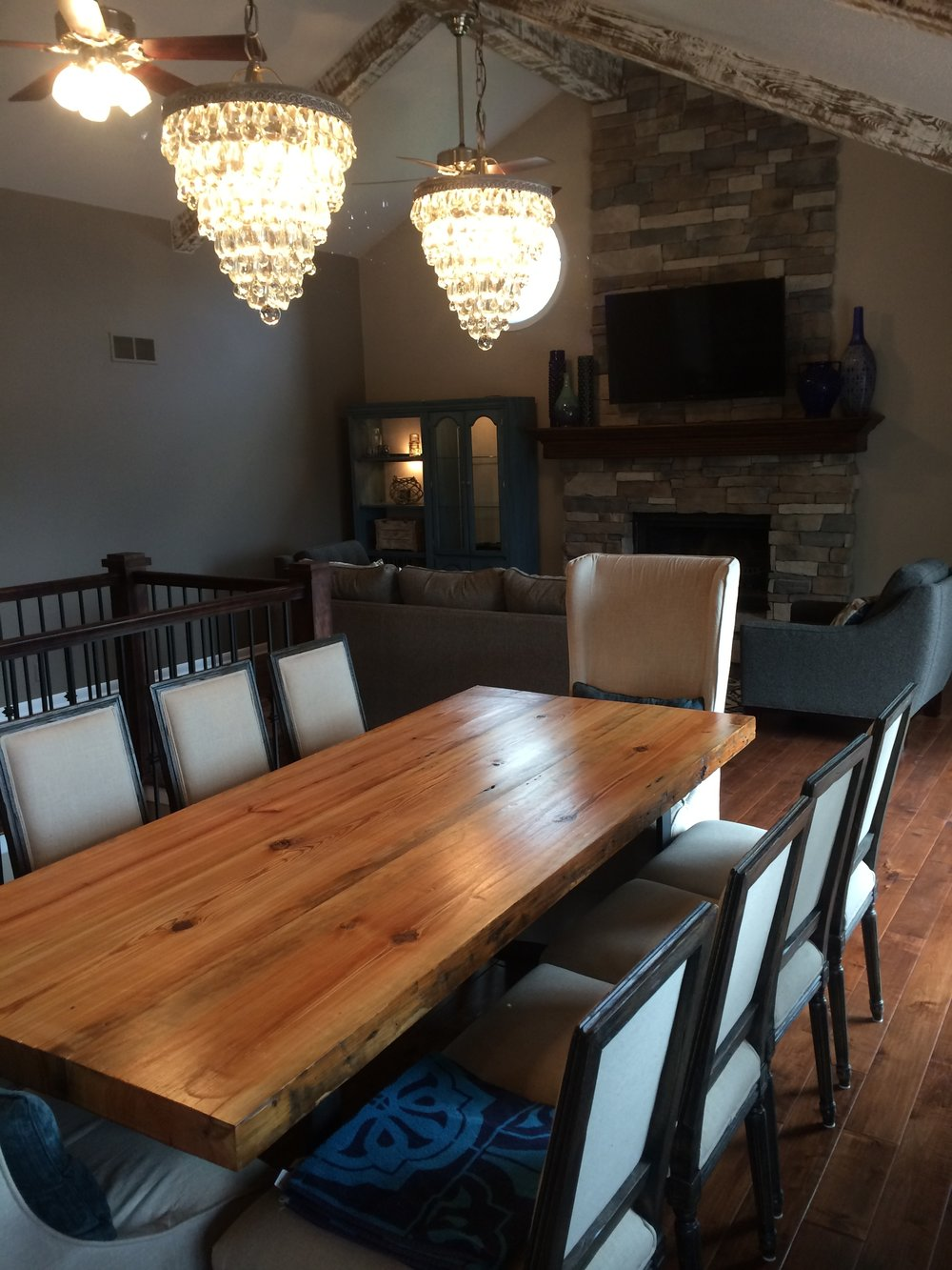 After - Wide open spaces with flowing hardwood floors, new custom lighting and floor to ceiling hand laid stone fireplace.  Also note the custom table made by Cody.
