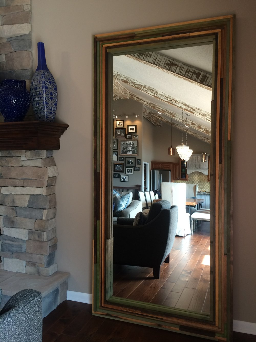 Custom made from old, stained lumber Cody found and rebuilt into a giant floor mirror to bounce even more light around the space.