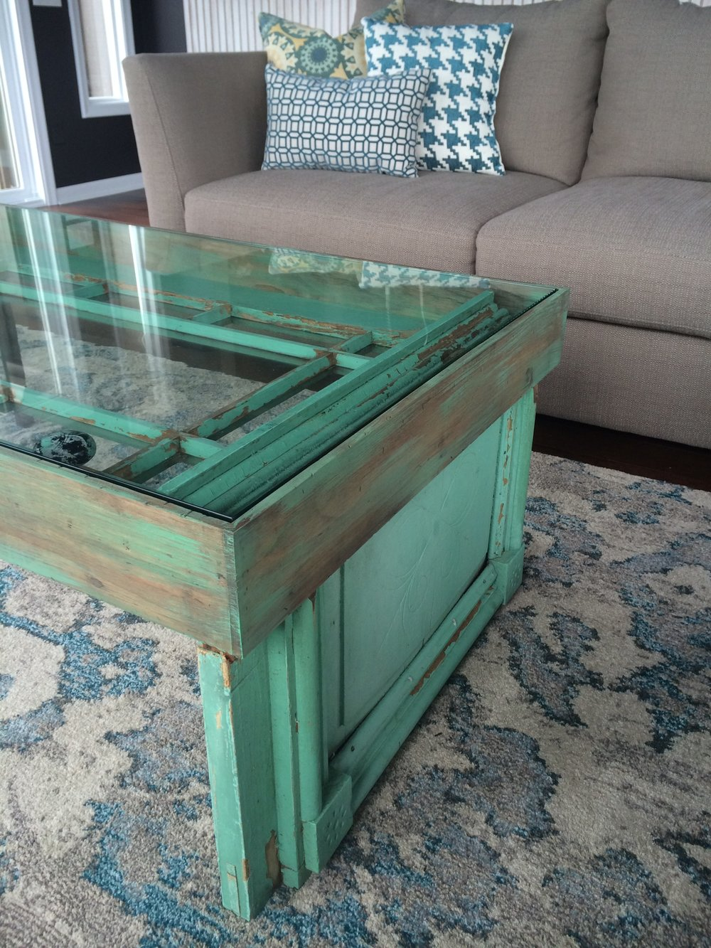 This old door that was hidden in the corner of the room, not only served as color inspiration for the sunroom but also was rebuilt by Cody into a coffee table.