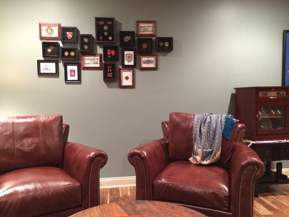 Every man cave needs a set of leather chairs to relax in and smoke a cigar. Behind you can see on the wall a custom wall display Cody created with all the metals our clients received while serving our country.