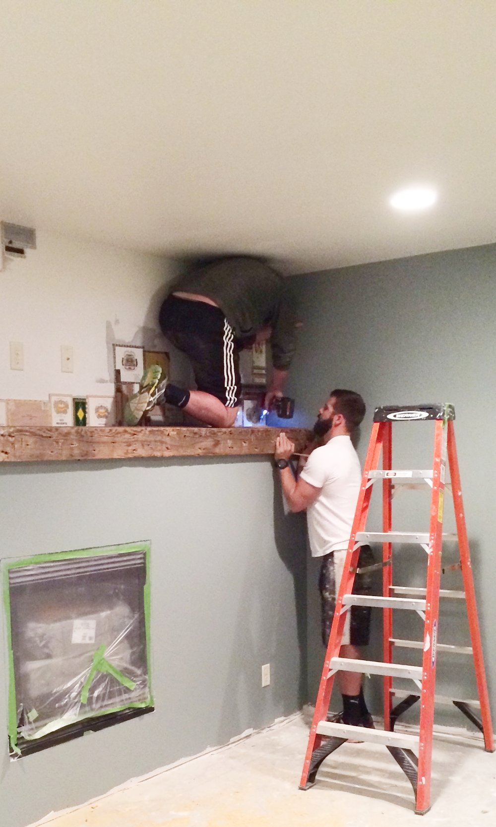 Cody and his brother Ryan seen here installing the massive vintage beam in the cigar lounge.