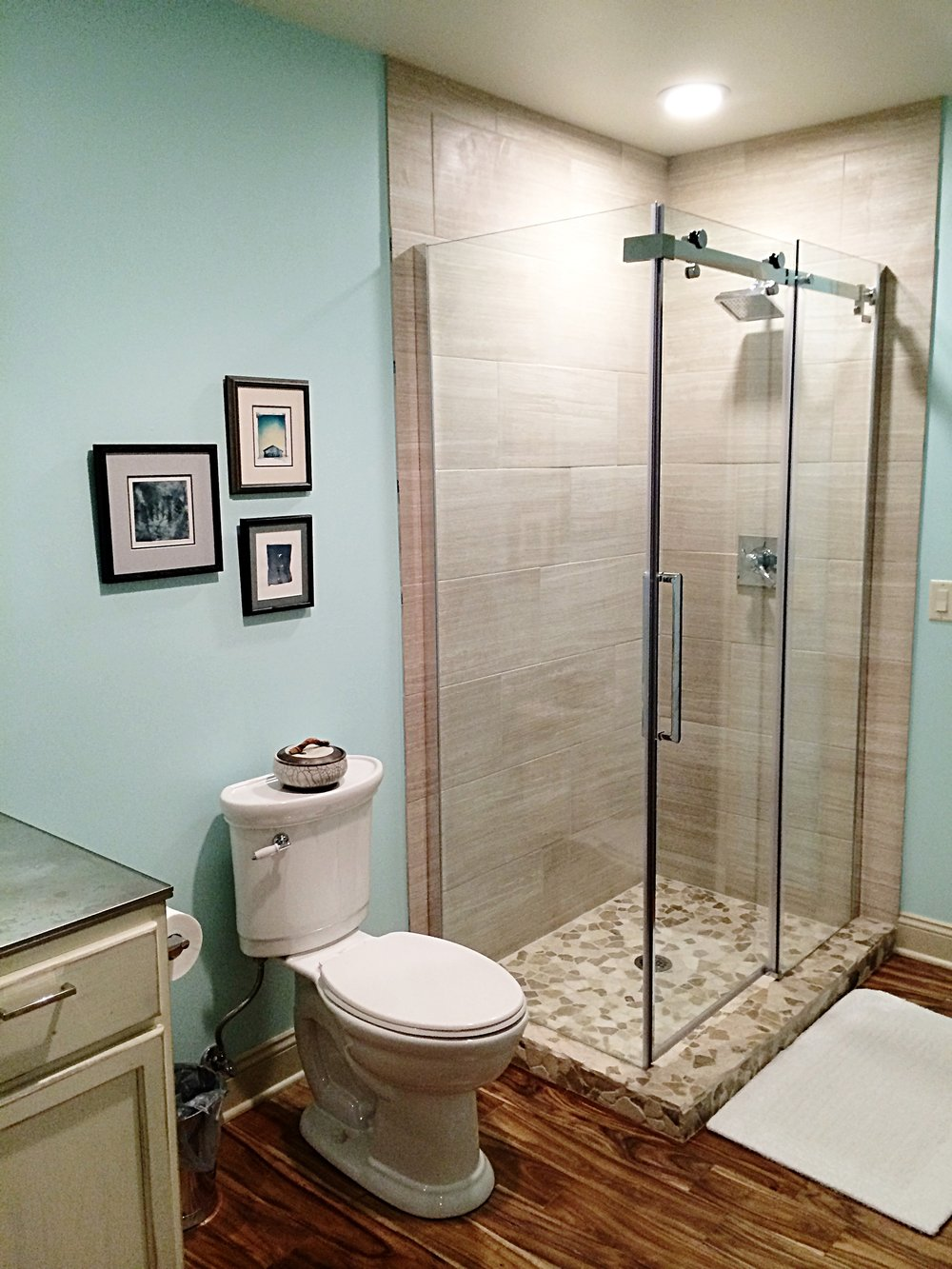 Tumbled stone flooring in the shower with a soft linen weave wall tile is the perfect contrast to the acacia wood floors and vintage style vanity!