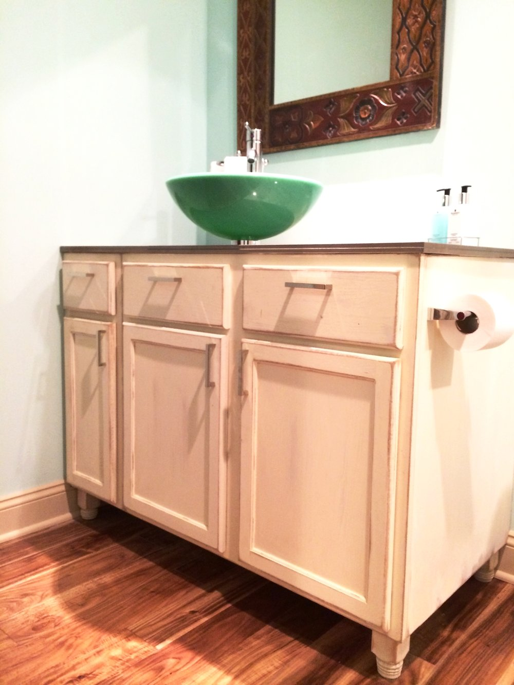 Cody created a custom vanity topped with an amazing acid stained glass top and sea green vessel sink.