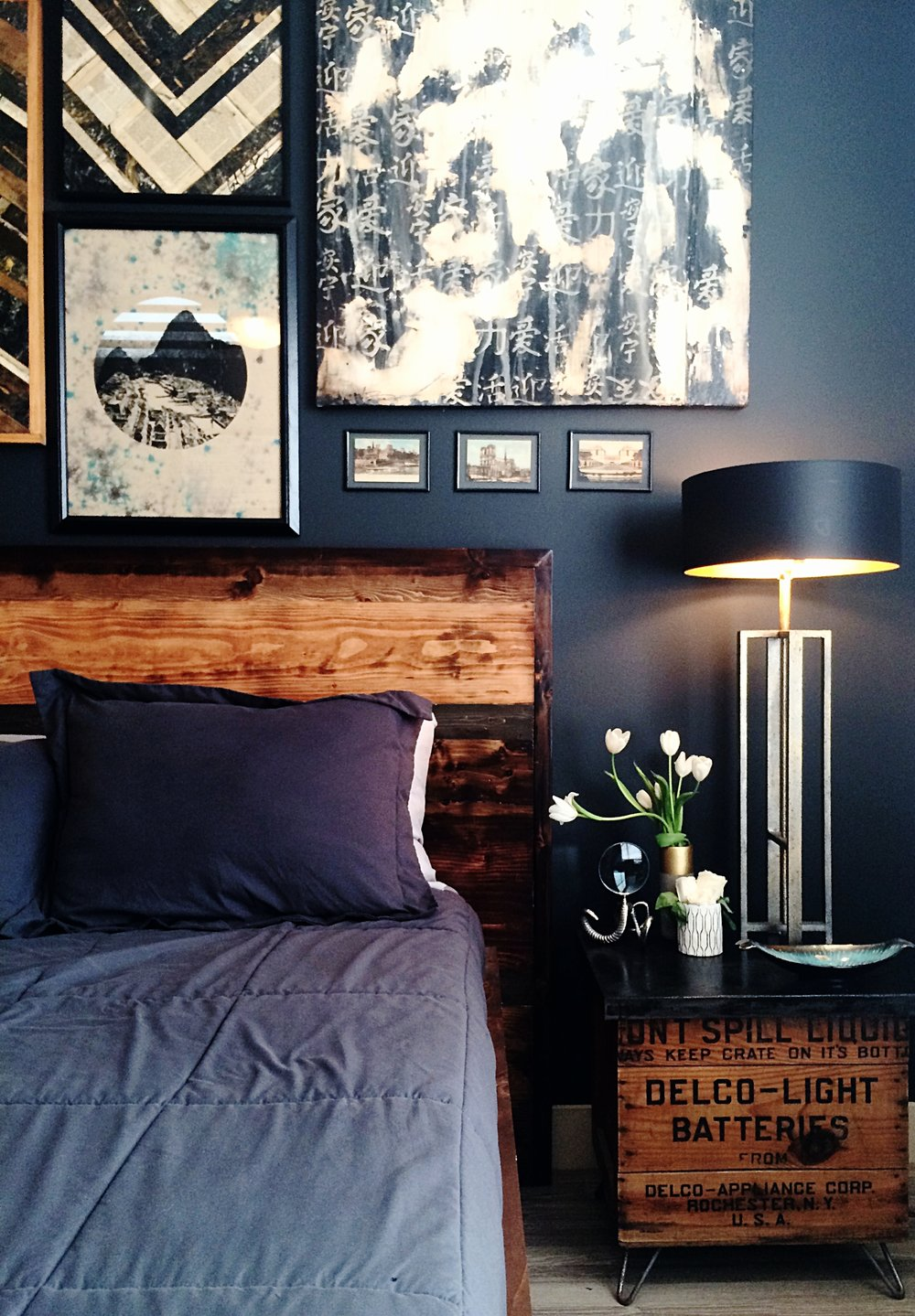 "Custom ""Jasper"" be with an acid stained cement top side table made out of a vintage delco shipping box. Custom art also by Cody graces the walls above the bed and a hand made lamp (also by him)"