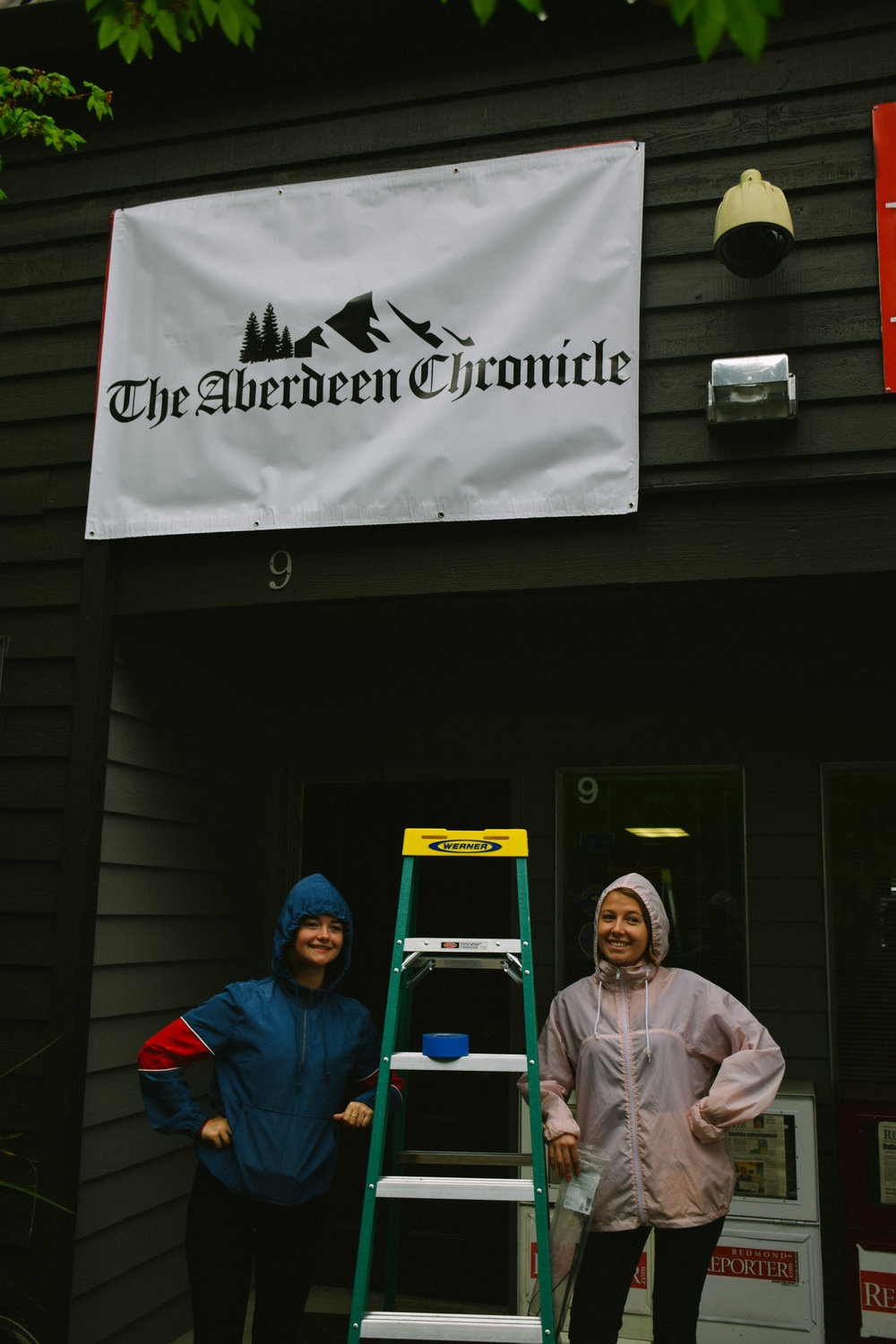 Producer, Sophia Hoefle, stands with Production Designer, Kate Dudek under the sign she designed for the local newspaper in the film.