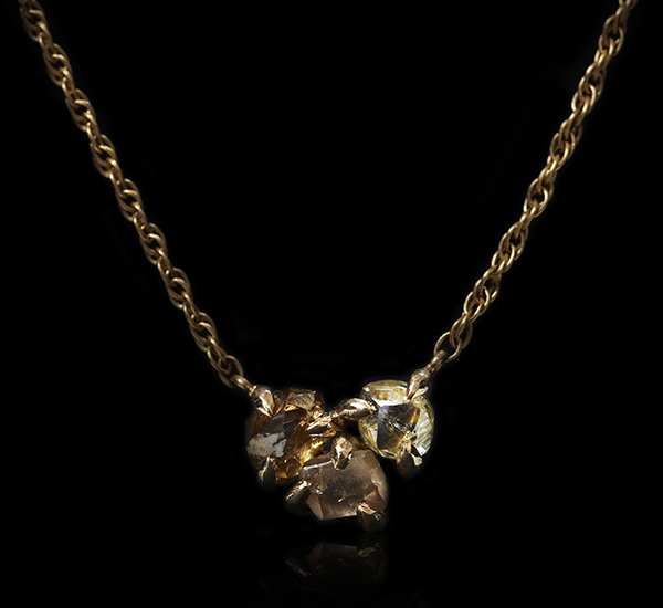 Three brown raw diamonds in a cluster in a gold necklace.