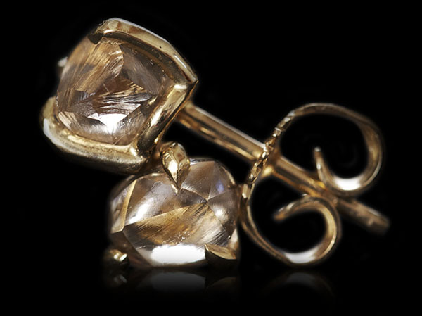 Brown Australian diamond earrings laying on top of each other.