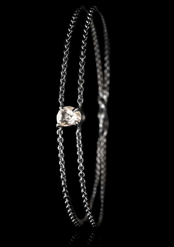 Oblong raw brownish diamond in a double black rhodinated chain bracelet.