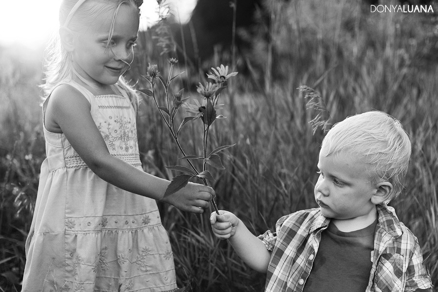Sister shares a flower with her brother for photos in the Woodlands