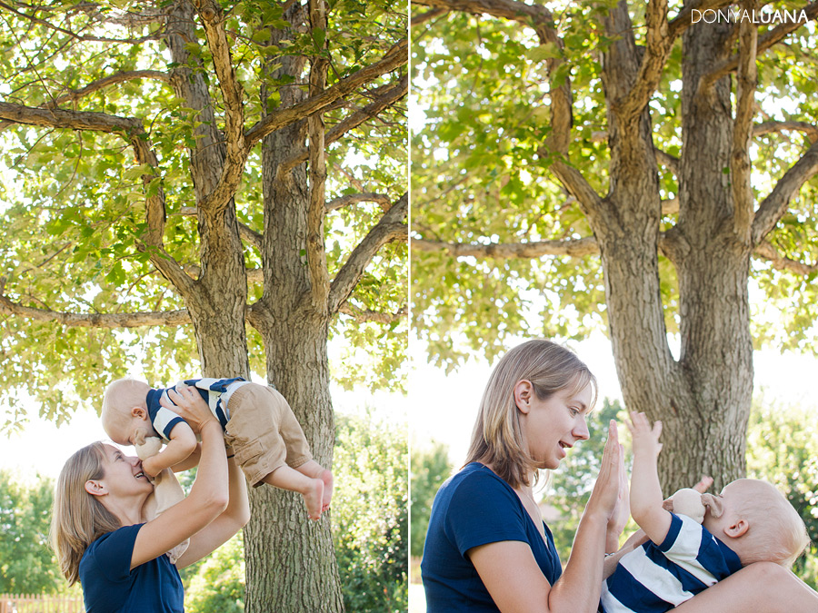 Mom holds one year old in front of trees at Burnsville Minnesota Park for Portraits
