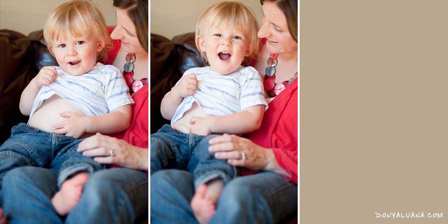 Toddler shows off belly button to mother during family photos