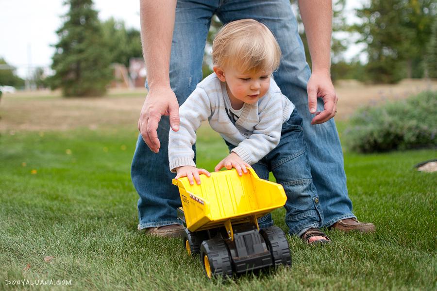 Trouble-making toddler runs through yard pushing tractor in Sugar Land Family Photos