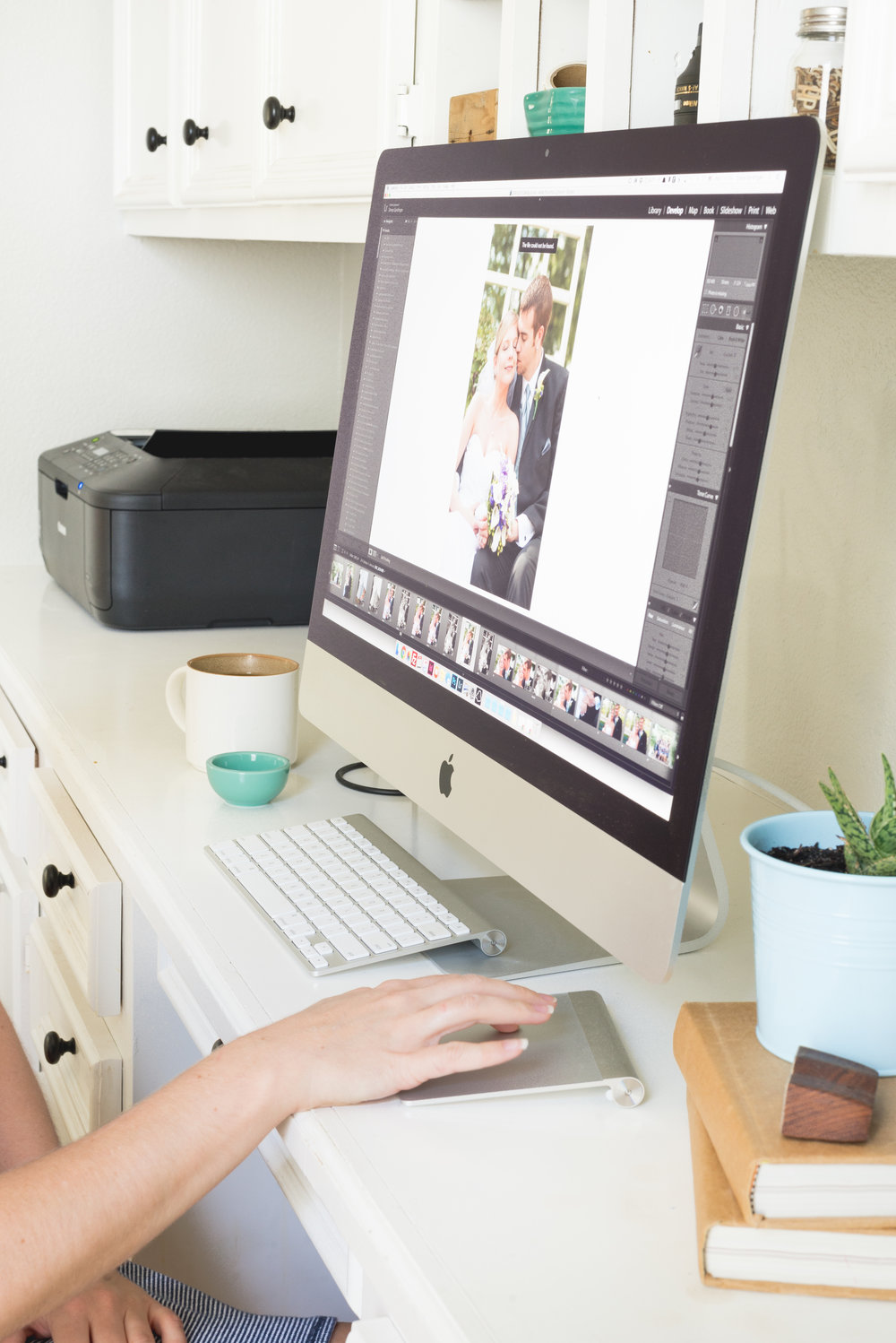 Photo editor working at desk and editing photos for a photographer who outsources.