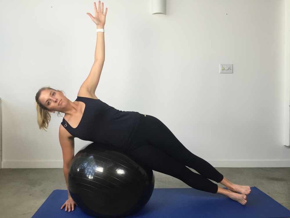 Side lying balance over ball without side leg raise  Begin by lying over the ball and balancing on your side. Arms are strong, ankle strong and lifting your body upwards to the ceiling.