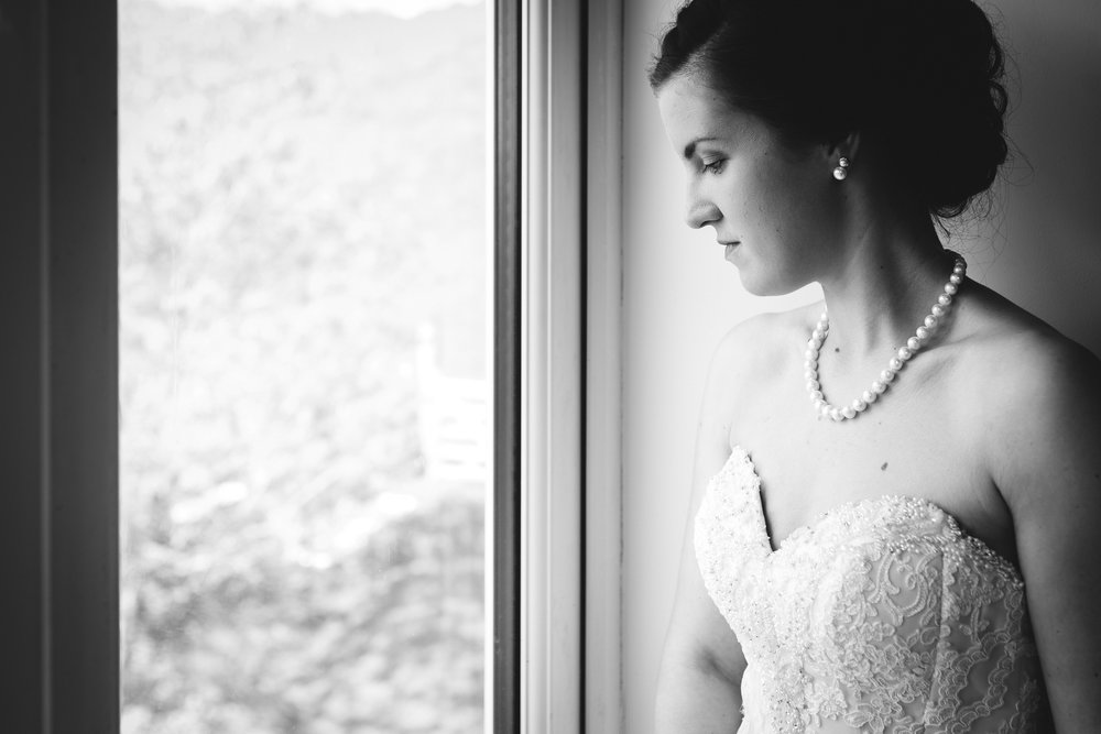 Bride in wedding dress looking out of window - Wedding Photography