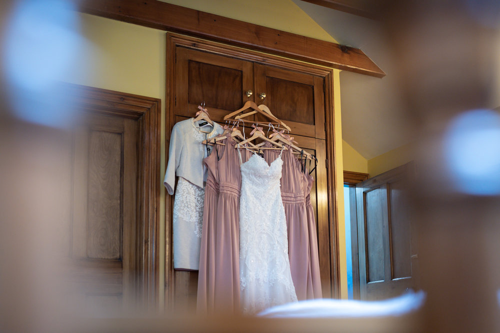 Wedding dress and bridesmaids dresses hanging up - Powys Wedding Photography