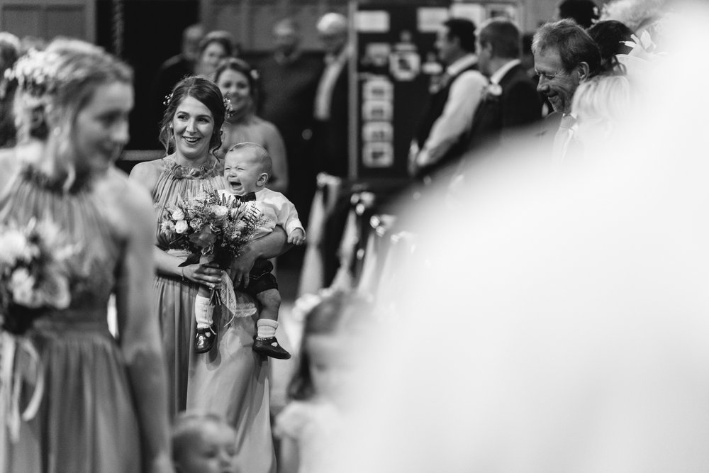 bridesmaid and crying baby walking down aisle - Powys Wedding Photography