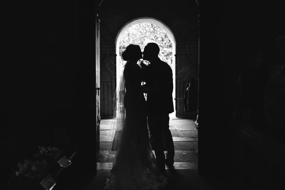 Bride and groom kiss in church door - Powys Wedding Photography