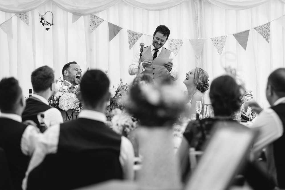Bride and Groom laughing at best man speech - Powys Wedding Photography