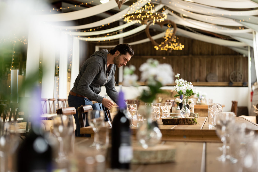 Steven Parry Photography / Groom Putting Finishing Touches to Tables / Sugar Loaf Barn