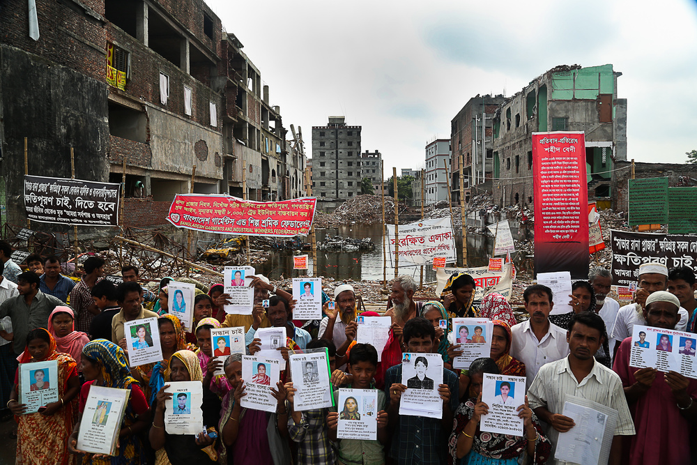 The loved ones of garment workers killed in the Rana Plaza collapse hold photos of the victims in protest (photo: Jason Motlagh)