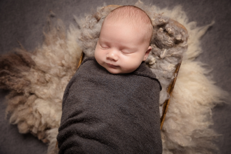 sleeping-newborn-posed-prop-swaddled