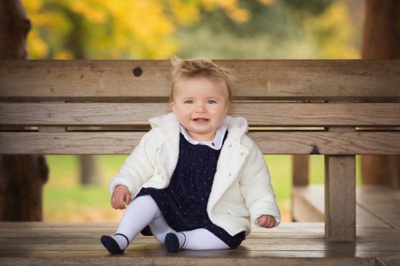 baby girl on park bench