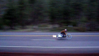 A Bob Maddox rocket bike being propelled at speed along a public road.