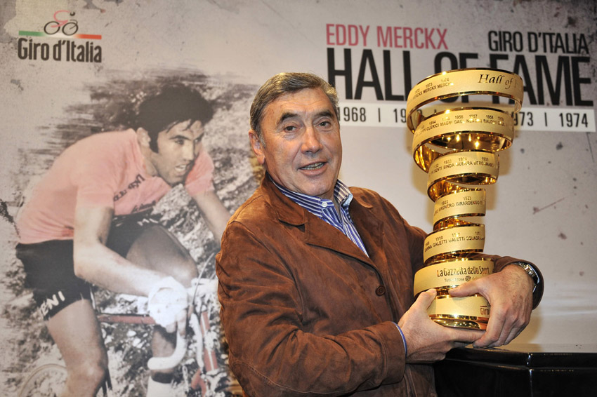 Eddy Merckx incontra la stampa, both hands firmly on the Giro D'Italia Hall of Fame trophy.