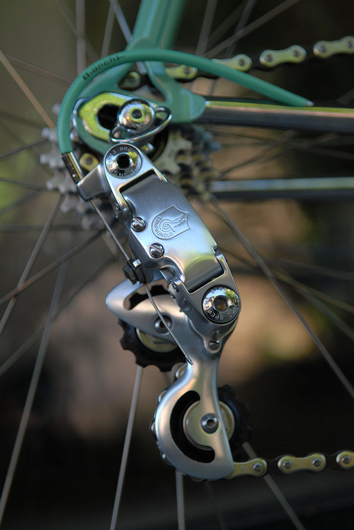 There were three versions of the Gen 1 Campagnolo C Record rear derailleur. This rear mech is the third cage type with slots cutout in the top and the bottom of the cage. The other type had only the bottom part of the cage cutout and the most well known version had no cutouts. This cutout version is sometimes referred to as a Gen 1.5 Corsa Record rear mech.