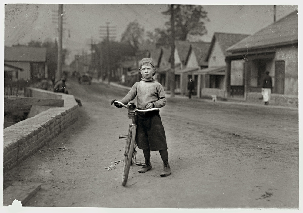 "Isaac Boyett, ""I'm de whole show."" Waco, Texas ""The twelve year old proprietor, manager and messenger of the Club Messenger Service, 402 Austin Street, Waco. The photo shows him in the heart of the Red Light district where he was delivering messages as he does several times a day. Said he knows the houses and some of the inmates. Has been doing this for one year, working until 9:30 P.M. Saturdays. Not so late on other nights. Makes from six to ten dollars a week."" November 1913"