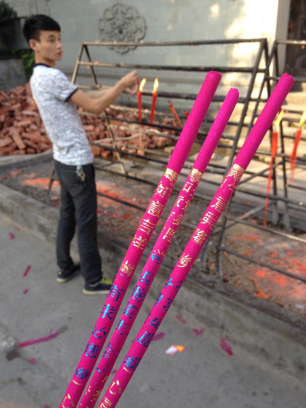 Lighting incense sticks.