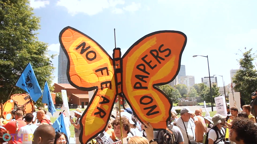 "The image of the butterfly, created by Favianna, is now used by immigration activists across the nation. Image is a cardboard butterfly which reads ""No Fear, No Papers"" on the wings. It is being held at a march. Image via  Raconteur.la"