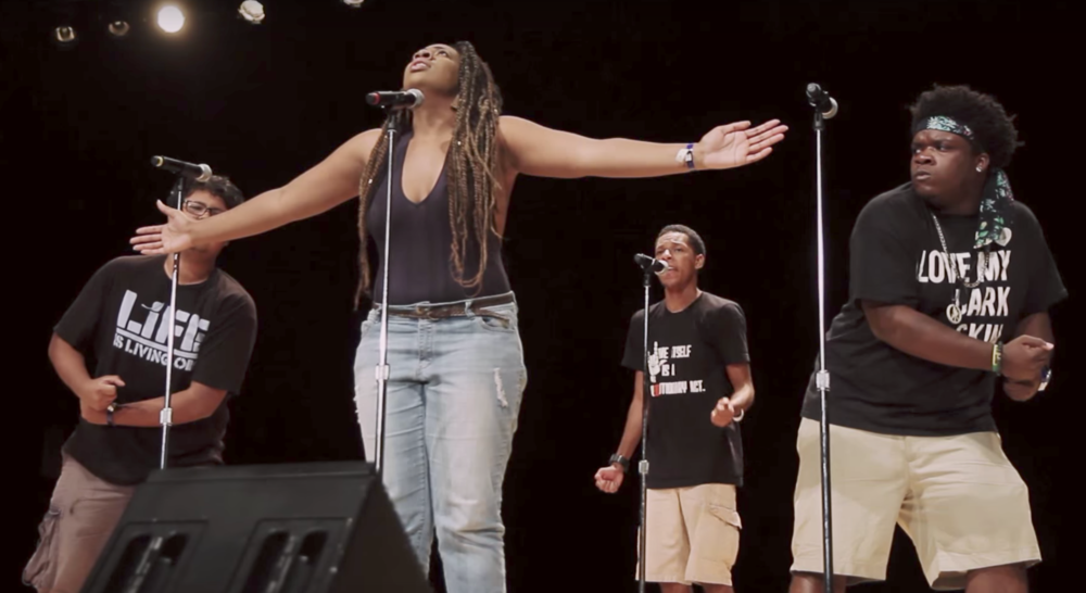 "Image of three young poets of color performing on stage with a black background. Three individuals with short hair stand in the back wearing black t-shirts and khaki shorts; an individual with long braided hair wearing a black shirt and jeans stands in front, with their arms extended. Screenshot of of the Atlanta Team performing their poem ""Rosa Parks"" at the 2015 Brave New Voices Finals."
