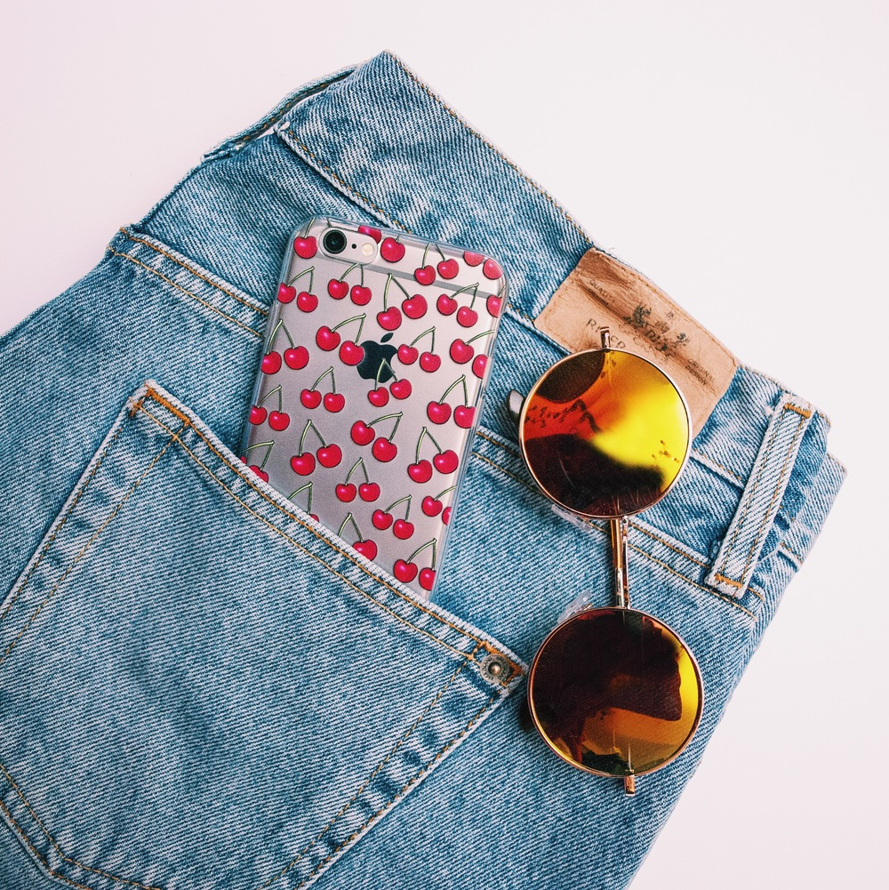 Inkase Cherry iPhone case with denim jeans and cool sunglasses.
